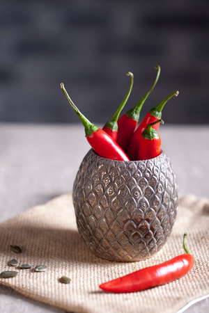 bagging: Chili peppers in a metal exotic vase on a bagging textile