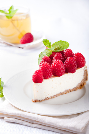 Cheesecake slice with fresh raspberry and mint leaves