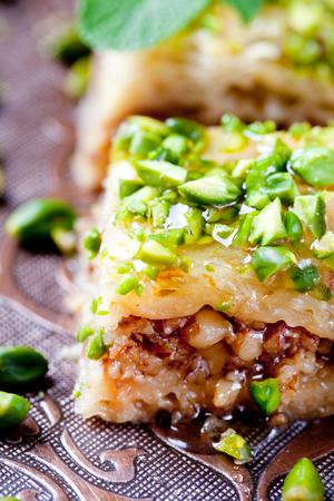comida arabe: Pistacho turco y phyllo pastelería postre, baklava en una bandeja de cobre auténtico con una placa de pistachos y rama de canela Foto de archivo