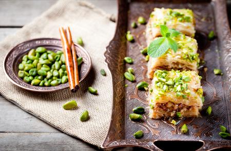 comida arabe: Pistacho turco y phyllo pasteler�a postre, baklava en una bandeja de cobre aut�ntico con una placa de pistachos y rama de canela Foto de archivo