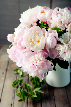 romantic flowers: Bunch of peony flowers with green leaves in an enamel jar on a wooden background Stock Photo