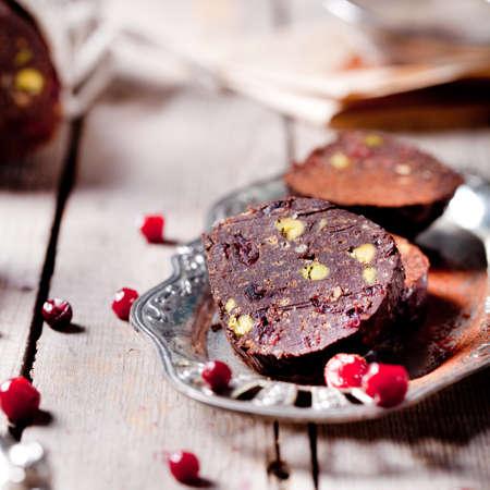 weihnachtskuchen: Schokoladendessert Salami mit Pistazien, Hafen und Preiselbeeren auf Holzuntergrund.