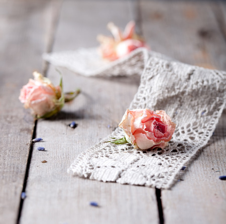 purpule: Dried roses with cage work on a wooden surface. Floral background