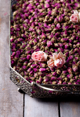 Dried roses and rose buds in a vintage tray on a wooden background