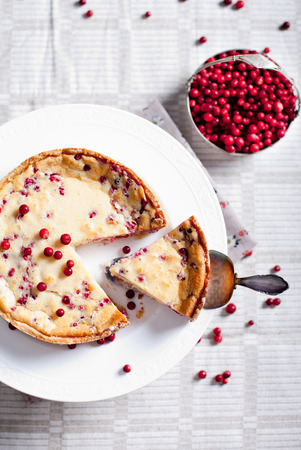 White chocolate cheesecake tart with cranberries, billberries on a white plate photo