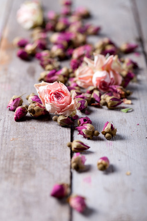 Dried rose buds scattered on a grey wooden table