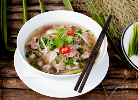 sopa de pollo: Tradicional sopa de carne pho vietnamita en un fondo de madera