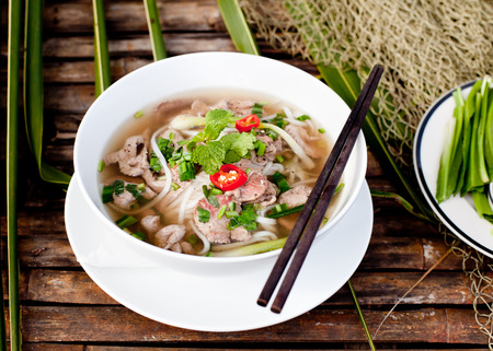 rice noodles: Traditional Vietnamese beef soup pho on a wooden background