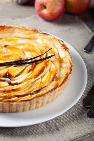 French apple tart with apple compote and vanilla on a white plate photo