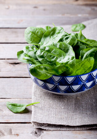 Baby spinach in a blue ceramic bowl on a wooden background photo