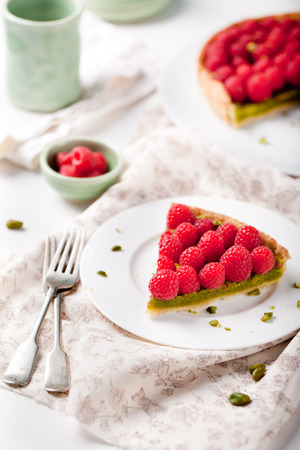 Fresh raspberry and pistachio cream tart on a white textile background. photo