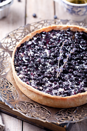 Blueberry, bilberry tart with lavender on a vintage  plate on a wooden background photo