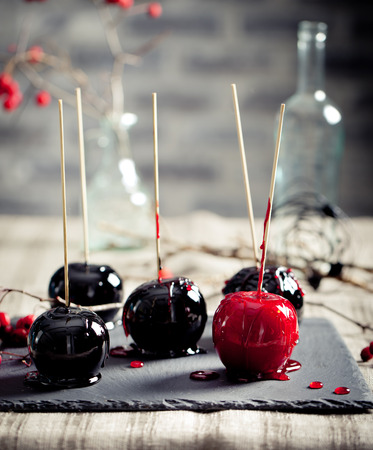 taffy: Halloween black and red caramelized apples on a wooden sticks. Traditional dessert. Selective focus.