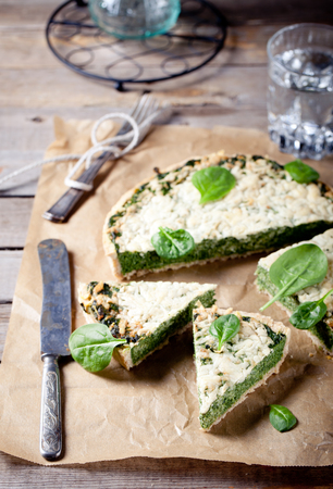 gruyere: Spinach and Gruyere cheese tart on a wooden background