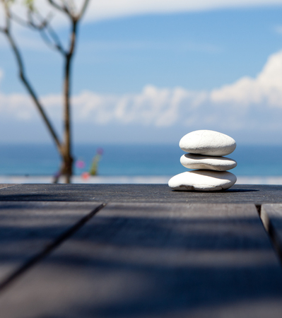 simple life: Stack of pebble stones at the beach on a wooden surface