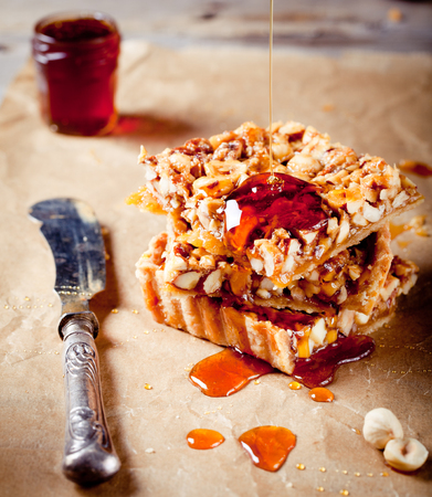 maple syrup: Nuts,maple syrup and honey caramel tart on a wooden background