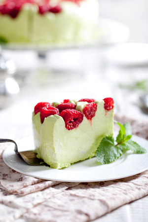 gass: Pistachio mousse cake, cheesecake with fresh raspberry on white plate with mint leaves