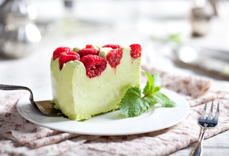 Pistachio mousse cake, cheesecake with fresh raspberry on white plate with mint leaves
