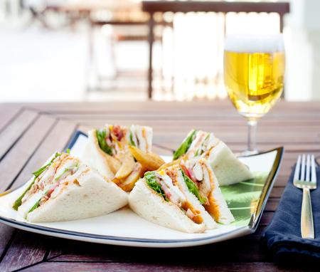 sandwich de pollo: Club sándwich con papas fritas y un vaso de cerveza en una mesa de madera