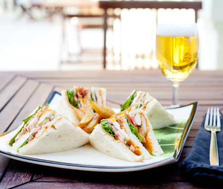 breakfast sandwich: Club sandwich with french fries and a glass of beer on a wooden table