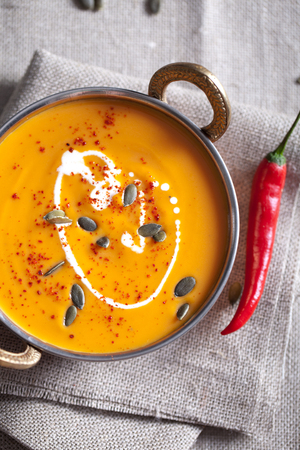 brassy: Pumpkin cream-soup with chili and seeds in a copper bowl