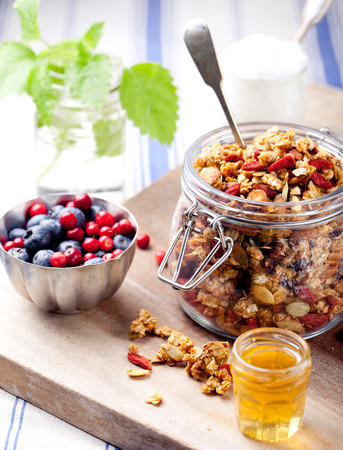 Healthy breakfast. Granola with  honey, yogurt and fresh berries in a glass on blue and white background. Фото со стока