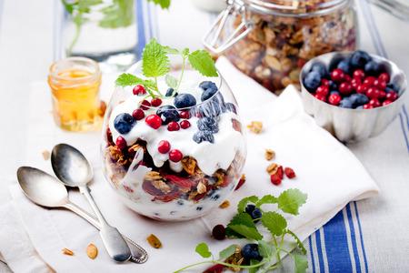 Gezond ontbijt. Muesli met bessen, honing, yoghurt en verse bessen in een glas