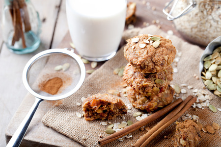 milk and cookies: Oat and peanut butter cookies with pumpkin seeds and cinnamon with a glass of milk on a wooden background. Stock Photo
