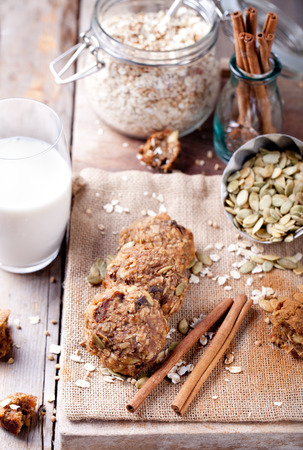 oatmeal cookie: Oat and peanut butter cookies with pumpkin seeds and cinnamon with a glass of milk on a wooden background. Stock Photo