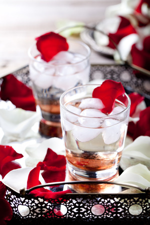 stratification: Rose flavor cocktail with ice cubes in glasses with rose flower petals on a vintage tray Stock Photo