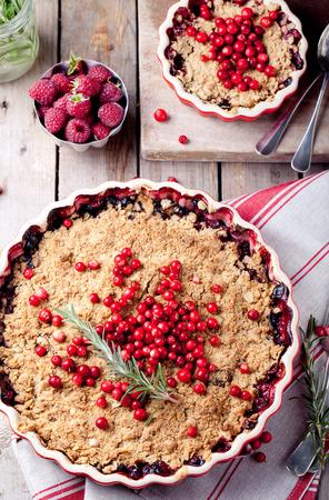 Cranberry, bosbes crumble met rozemarijn op een houten en textiel achtergrond
