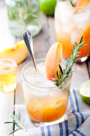fizz: Peach and rosemary fizz cocktail on a wooden background.