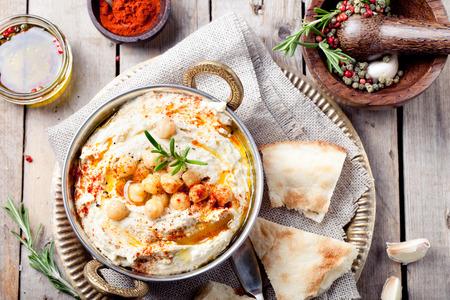 Hummus, ceci tuffo, al rosmarino, peperoncino affumicato e olio d'oliva in una ciotola di metallo con pita Archivio Fotografico - 46252423