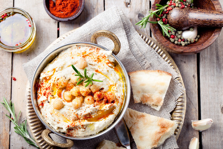 Hummus, chickpea dip, with rosemary, smoked paprika and olive oil in a metal bowl with pita