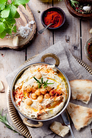 Hummus, kikkererwten dip, met rozemarijn, gerookte paprika en olijfolie in een metalen kom met pita
