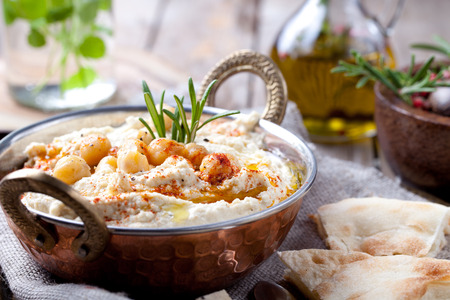 arabic food: Hummus, chickpea dip, with rosemary, smoked paprika and olive oil in a metal bowl with pita