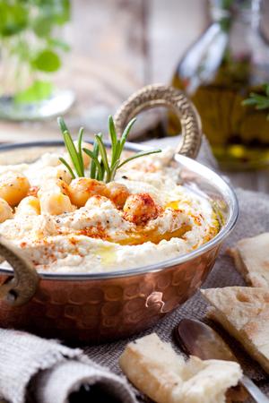 comida arabe: Hummus, dip de garbanzo, con romero, piment�n ahumado y aceite de oliva en un recipiente de metal con Pita Foto de archivo