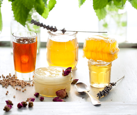 honey comb: Honey variaty with bees comb in a glass jurs with flowers and fresh herbs.