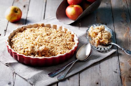 Crumble de manzana en el fondo de madera con manzanas