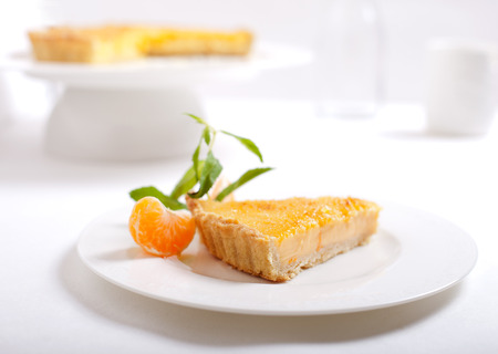 crema: Tangerine creme brulee tart on a white background with fresh mint leaves and piece of tangerine
