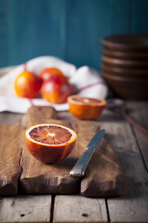 half cut: Sicilian Bloody oranges candied slices on a wooden cutting board