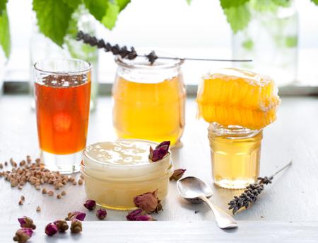 rosas blancas: Variedad Miel con panal de abeja en unos tarros de cristal con flores y hierbas frescas.