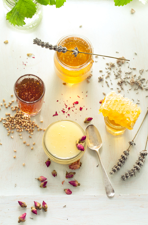 honey comb: Honey variety with bees comb in a glass jars with flowers and fresh herbs.
