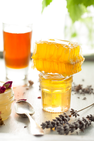 orange rose: Honey variety with bees comb in a glass jars with flowers and fresh herbs.