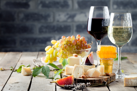 camembert: Grape, cheese, figs and honey with a glasses of red and white wine on a stone and wood background