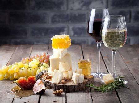 Druif, kaas, vijgen en honing met een glazen rode en witte wijn op een steen en hout achtergrond