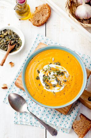 Roasted pumpkin and carrot soup with cream and pumpkin seeds on white wooden background. Copy space
