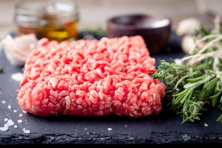 carnes rojas: La carne picada en un tablero negro piedra pizarra con hierbas frescas