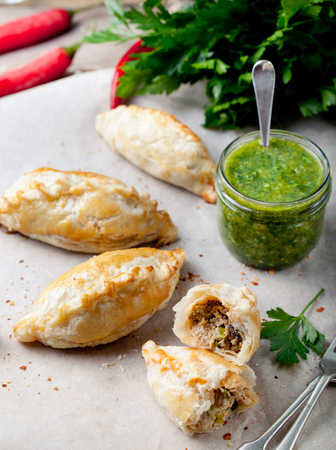 pasty: Empanadas with ground meat and green chili sauce. Traditional mexican dish. Stock Photo