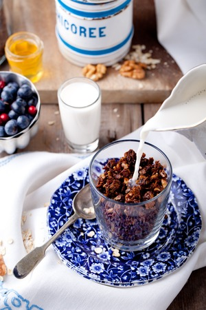 molasses: Oatmeal granola glazed with molasses and coffee, milk and fresh berries on a wooden background. Selective focus